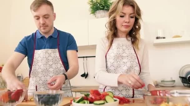 Porträts eines verliebten Paares, das in der Küche einen Salat zubereitet.