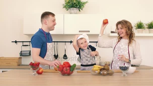 Rodina se připravuje salát v kuchyni. Táta a máma zvracet apple. Syn se usmívá