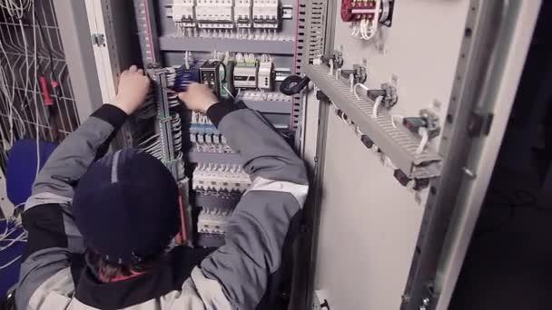 Muži, kteří pracují s dráty v elektroměru.