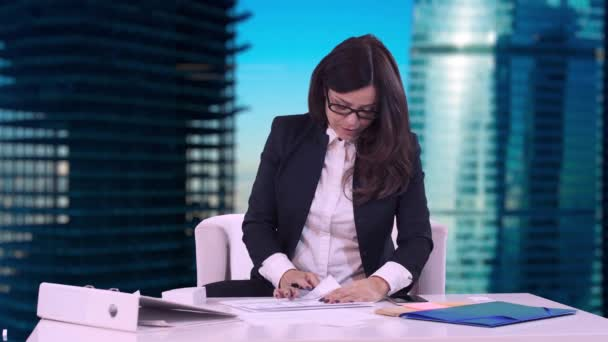 Portrait of a business woman. Brunette in glasses sitting in the office and signs the documents brought by the employee.