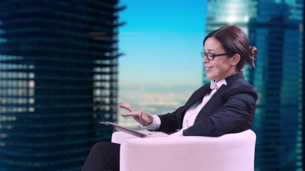Business woman with glasses sitting in the Studio in a business suit and gives interviews. Writes information on the screen and smiles.