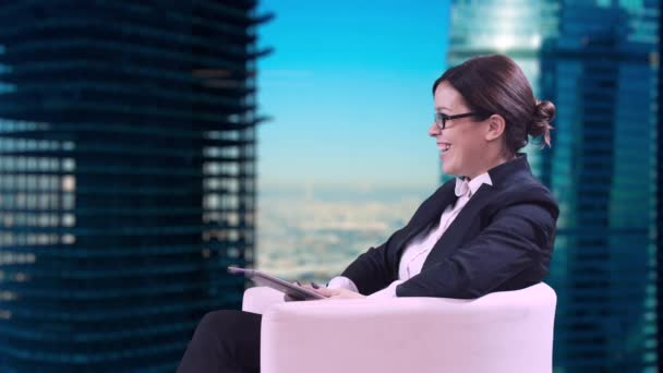 The TV Studio. Business woman with glasses sitting in the Studio in a business suit and gives interviews. Writes information on the screen and smiles.
