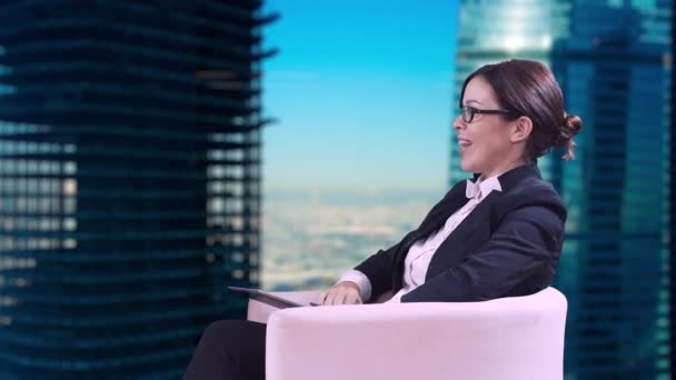 The TV Studio. Closeup of brunette in glasses. She sits in the Studio in a business suit and gives interviews.