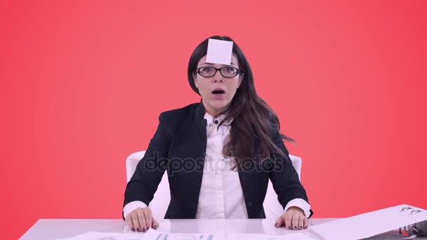 Portrait of young business woman in the office. Brunette in glasses removes the stuck piece of paper from his forehead.