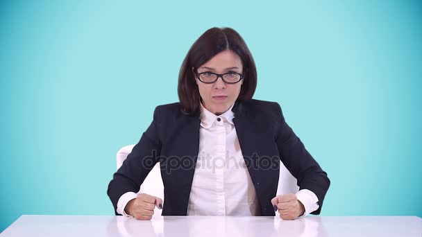 Beautiful brunette with glasses sitting in a business suit at office Desk and shouts. Blue background.