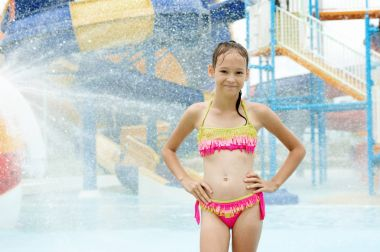 Smiling preteen girl standing under water drops. Blurred waterpa