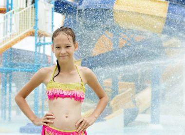 Smiling preteen girl standing under water drops. Blurred waterpa