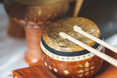 Old leather drum and drumsticks - membrane musical instrument. Ancient ethnic music on a folk festival. Timpani or kettledrums - old musical instruments in percussion family of classical orchestra.