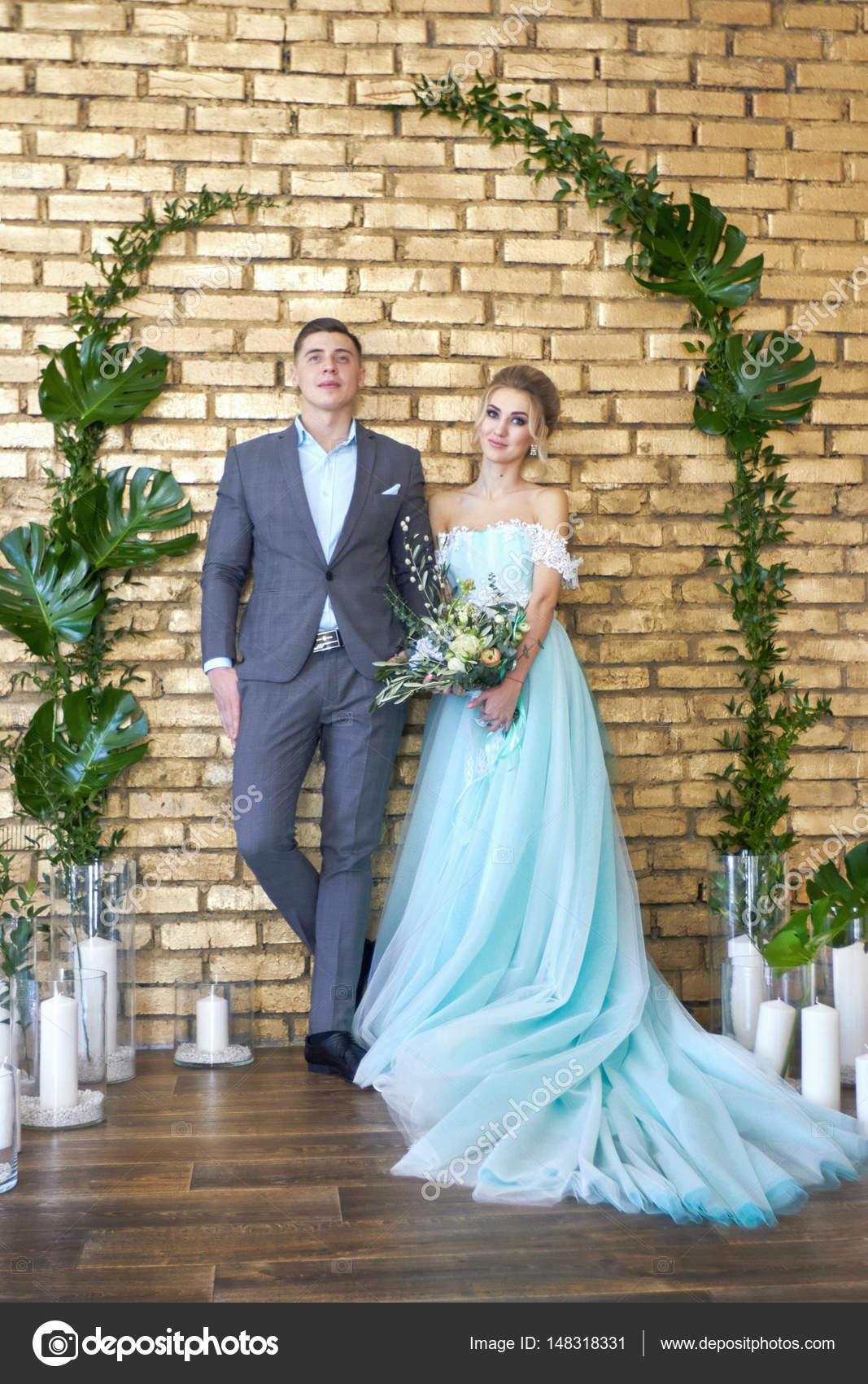 f1695f27942f2 Panna Młoda w turkusową sukienkę i pan młody niebieski garnitur. Wystrojem  ślubu, wesele zdjęcie strefy — Zdjęcie od ...