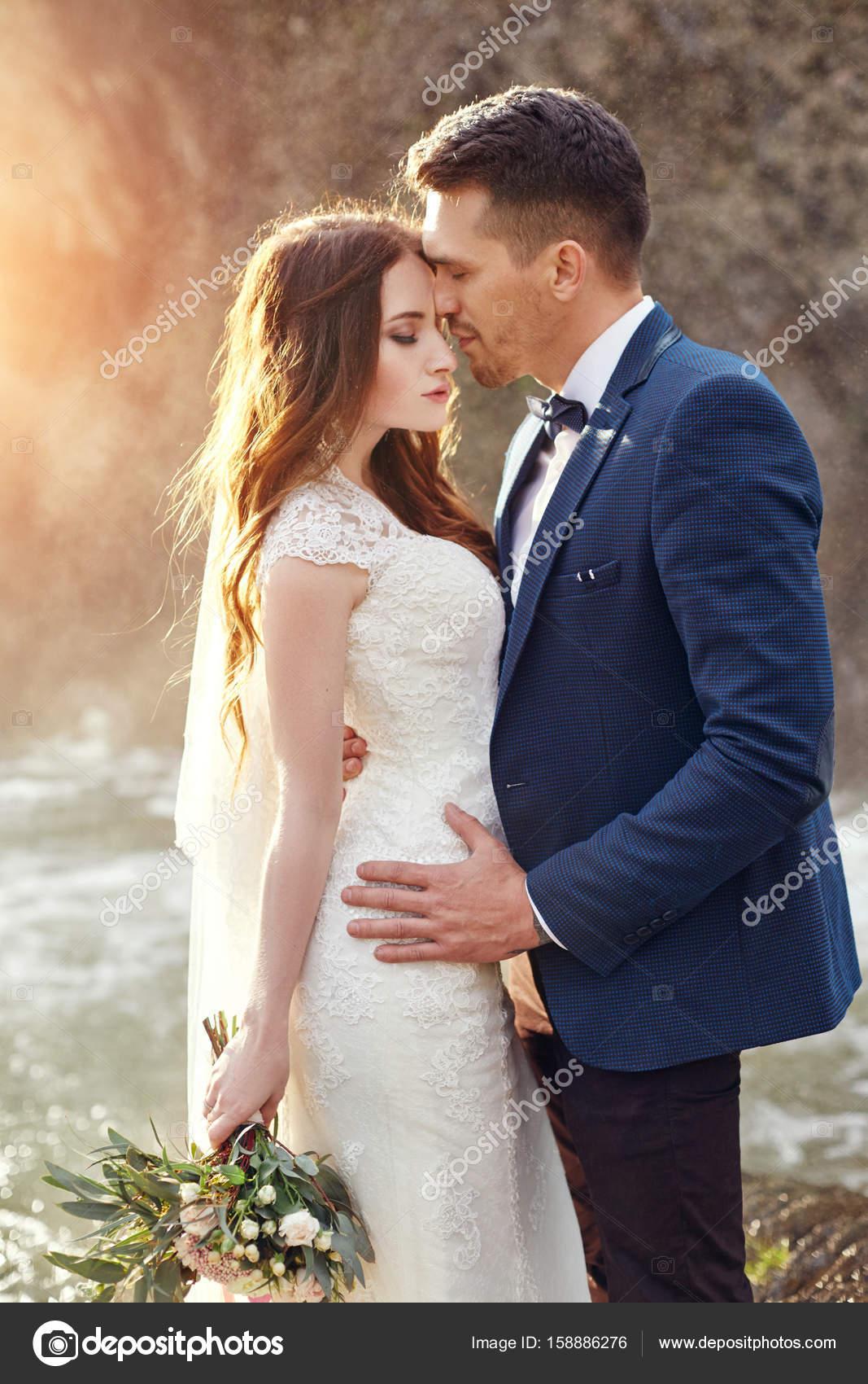 結婚式式の外。美しい花のブーケと新郎新婦。花嫁のためのウエディング ドレス。結婚式のカップルの抱っこが大好きです。ぼやけています。