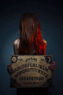 OUIJA Board for divination. Girl holding a OUIJA Board. Woman with long red hair Halloween. Mystic divination conversation with the spirits.