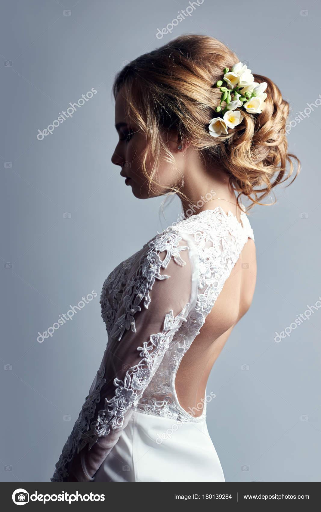 Junge Braut in einem luxuriösen weißen Brautkleid und schönes Haar ...