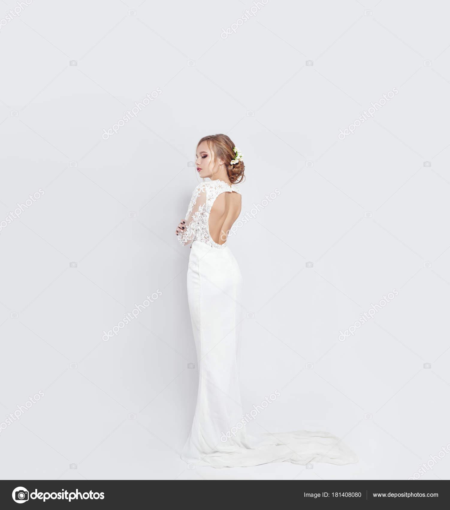 8234dbfcf032 Νύφη στο μακρύ λευκό νυφικό φόρεμα σε λευκό φόντο. Πολυτελές νυφικό στο  σώμα μιας γυναίκας