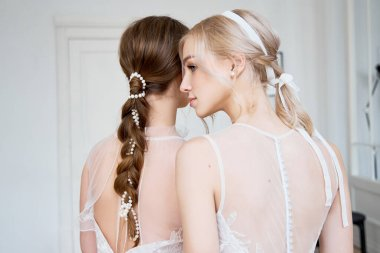 Two young girls of the bride embrace. New collection of wedding dresses for women. Wedding ceremony, the happiest day of your life