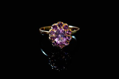 Beautiful golden ring with purple gemstone isolated on black background
