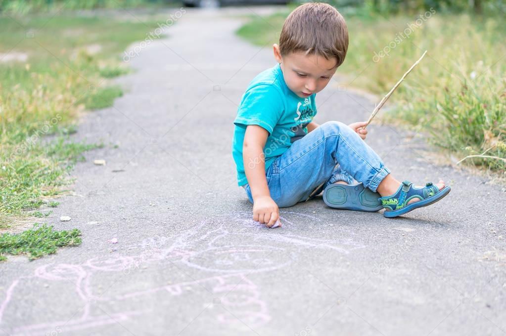 Süßes Kind junge zeichnen mit Kreide auf dem Bürgersteig im Park ...