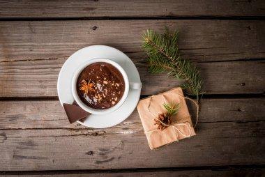 Hot chocolate mug and present on rustic table