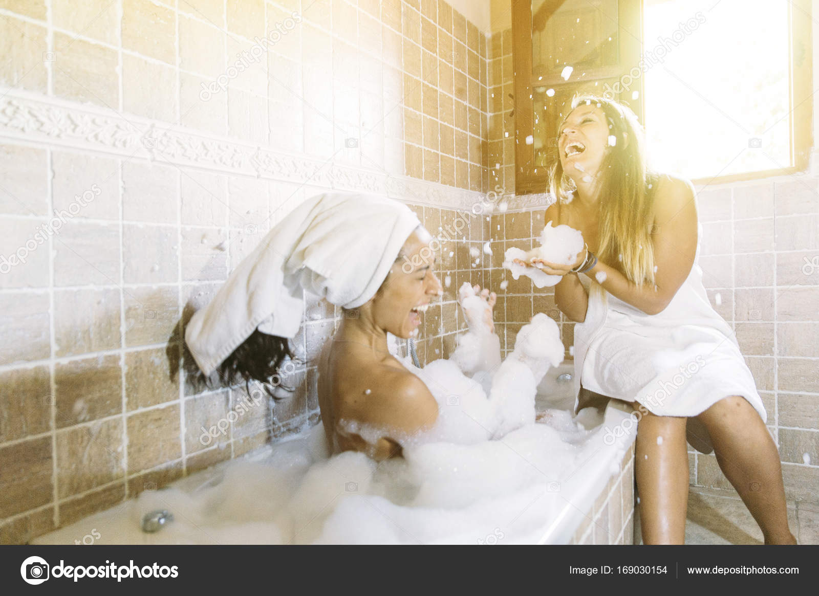 Two Happy Lesbians In The Bathroom Playing With Foam Stock Photo