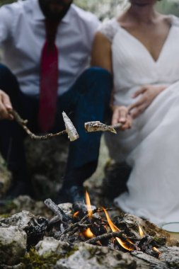 mutlu çift kamp ateşi yanında bankta oturmuş