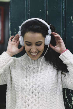 Happy girl smiling he listens to music with white earphones