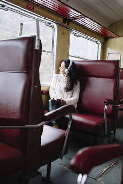 Teen passenger listening to the music traveling in a train