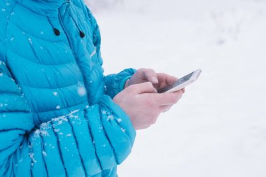 teenager with smartphone and blue jacket, snow day