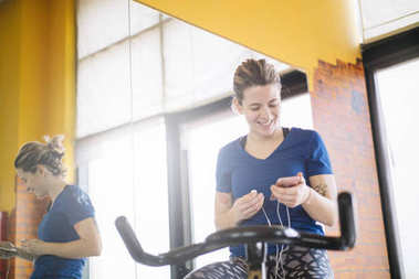 Woman practicing spinning at the gym  with smartphone
