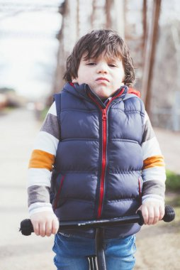 little boy playing outdoors with bicycle