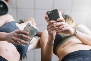 two woman with phone in gym