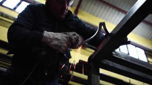 Man works with grinder cutting metal.