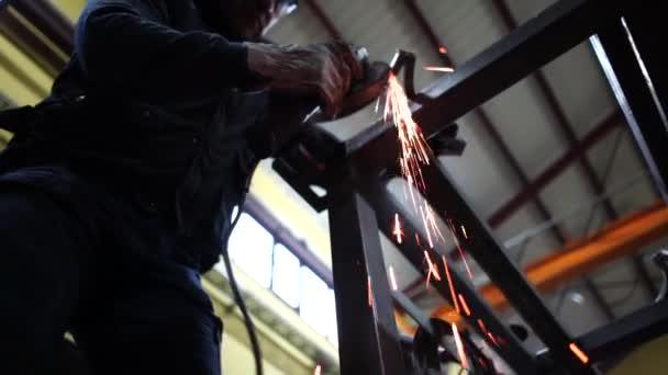 Mann arbeitet mit Schleifer, der Metall schneidet.