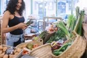 Egy nő, aki vásárolni gyümölcsök és zöldségek a zöldségesek