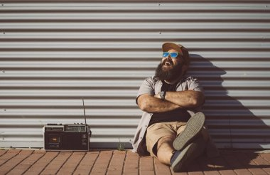 Man in the street wearing shirt and sunglasses with old school radio