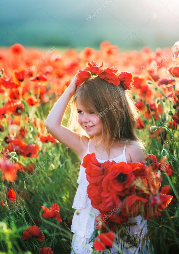 girl in poppy field holding flowers