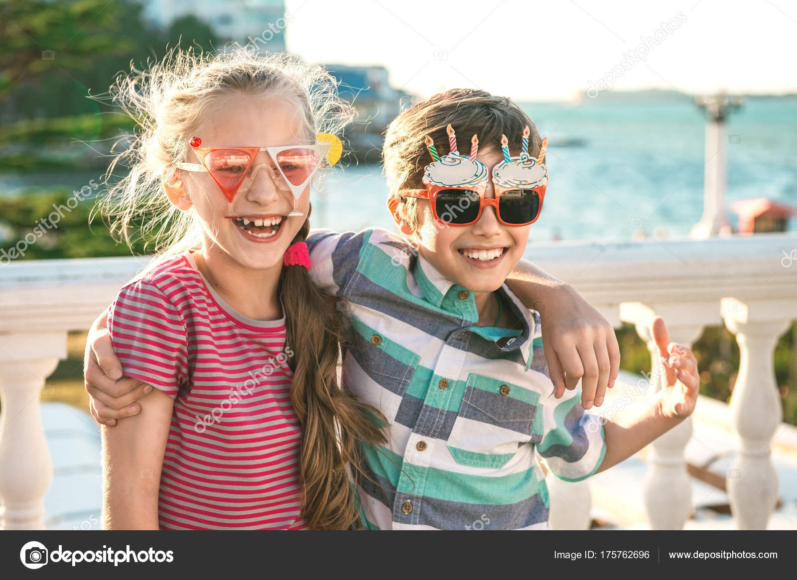 Portrait of two preteen children - boy and girl (9-10 years old) dressed in  funny party glasses having fun and birthday celebrations. 572d1c3e896d3