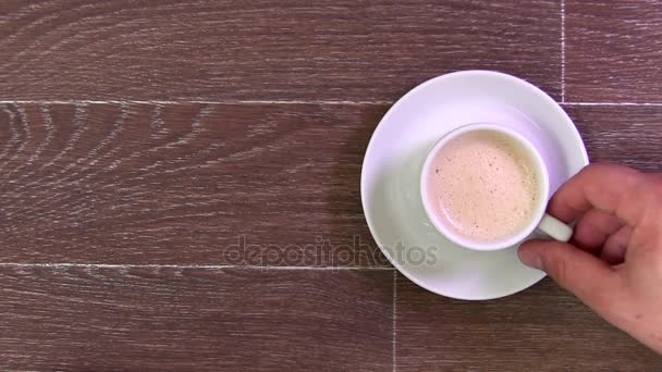 Mens Hand Takes a White Cup With Coffee And Drinks