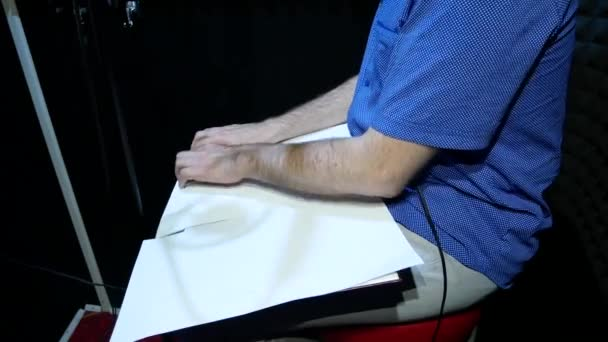 Photo Blind Man in Blue Shirt Reads Braille from the White Paper Sheet in Sound Recording Studio