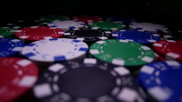Poker žetony Spin na stole v temnotě
