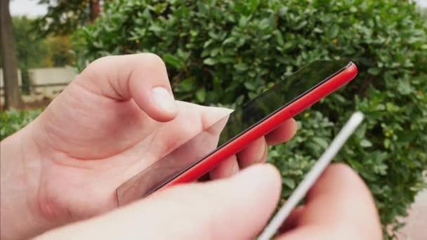 Muž pálivých červených smartphone a debetní nebo kreditní karty