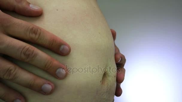 Mladý dospělý třese jeho tlusté břicho