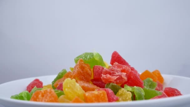 Candied fruit mix rotates on plate on white background