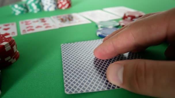 Hazardní hráč pohybuje pokerové žetony na stole v kasinu