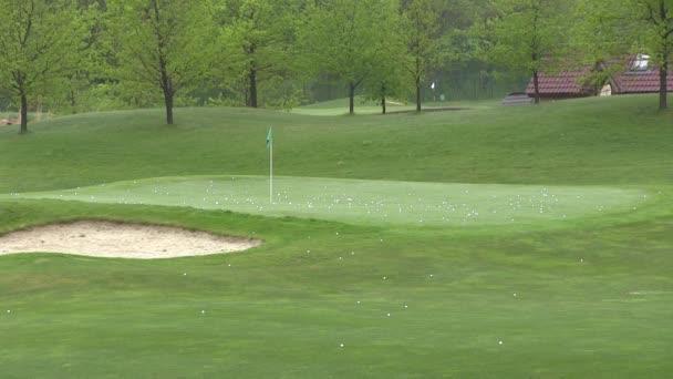 Golfovým hřištěm v klubu a zelené trávy s golfové míčky