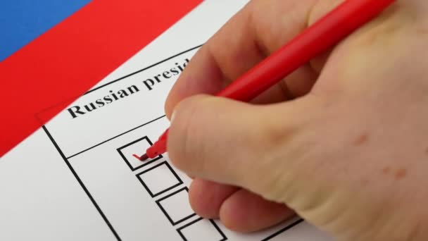 Hand voting in a ballot by red pencil with national flag of Russia