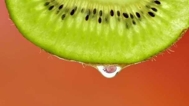 ein Tropfen reines Wasser oder Saft, der von einer Kiwi-Scheibe tropft