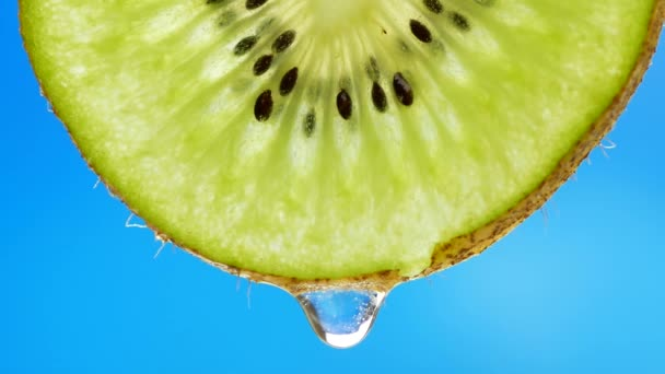 Drop of pure water or juice dripping from a slice of kiwi
