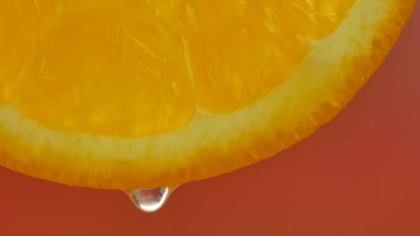 A drop of pure water or juice dripping from a slice of orange