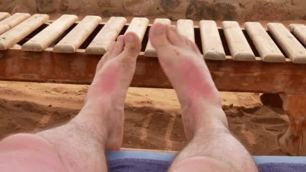 Pánské nohy relaxaci na pláži