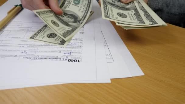 Ženská ruka hrabě americké dolarové bankovky na 1040 Daňový formulář