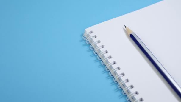 Papír jegyzettömb ceruzával kék háttér